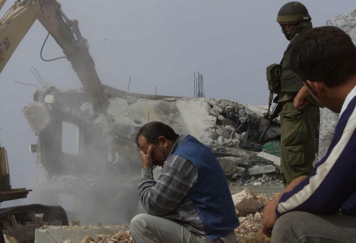 A Palestinian man can't look as his home is demolished
