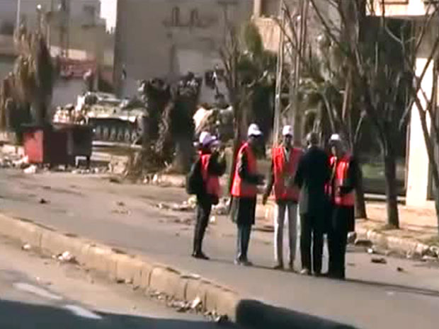 An image grab taken from a video uploaded on YouTube shows Syrian army tanks in the background as a group of Arab League observers tour the flashpoint central city of Homs on December 27, 2011 (Getty/AFP)
