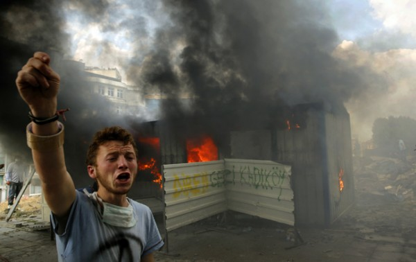 An anti-government protester shouts for help to extinguish a burning container in Istanbul's Taksim square