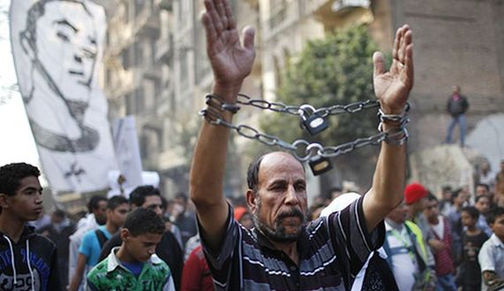 A mourner wearing chains attends the funeral of youth activist Gaber Salah, also known as Gika, at Tahrir in Cairo