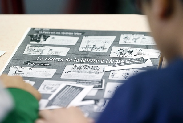 Children look at the chart on secularism in school on December 9, 2014 at the Louis Aragon school in the northern Paris suburb of Pantin on National Secularism Day.                                   AFP PHOTO / PATRICK KOVARIK        (Photo credit should read PATRICK KOVARIK/AFP/Getty Images)