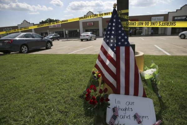 Police tape and a makeshift memorial sit on the lawn in front of an Armed Forces Career Center in this handout photo provided by the U.S. Navy, where earlier in the day a gunman opened fire, injuring one U.S. Marine in Chattanooga, Tennessee, July 16, 2015,  REUTERS/Damon J. Moritz/U.S. Navy/Handout via Reuters