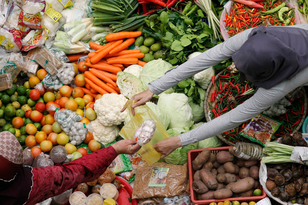 "A Muslim trader attends to her customer at a market ahead of Eid al-Fitr celebrations in Malaysia's northeastern town of Kota Bharu August 6, 2013. Eid al-Fitr, ""the day of celebrations"", marks the end of the fasting month of Ramadan. REUTERS/Bazuki Muhammad (MALAYSIA - Tags: SOCIETY RELIGION BUSINESS)"